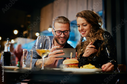 Fotografie, Tablou Cute caucasian fashionable couple sitting in restaurant at dinner and taking selfie