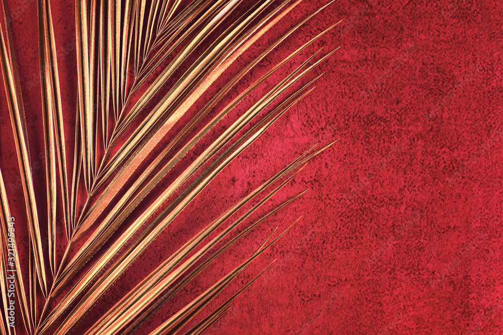 Closeup of golden palm leaf on abstract bright red textured background. Tropical conceptual luxury elegant trendy art deco summer background. Flat lay. Open composition, copy space.