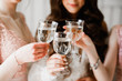 Photo bride with her friends drinking champagne from glasses