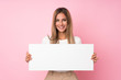 Young blonde woman over isolated pink background holding an empty white placard for insert a concept