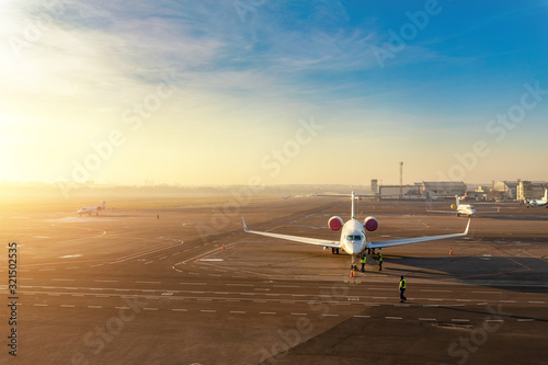 Obraz Colorful scenic dramatic morning sunset at airport asphalt taxiway and parking with different commercial passenger airplanes and private jets ready dor departure. Flight tickets booking and charter - fototapety do salonu