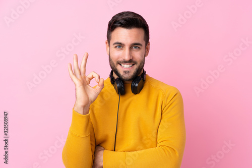 Fotografie, Obraz Young handsome man with earphones over isolated pink background showing ok sign