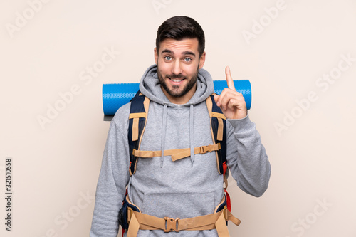 Obraz Young mountaineer man with a big backpack over isolated background pointing with the index finger a great idea - fototapety do salonu