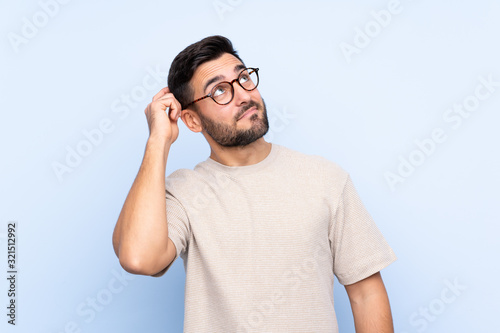 Fotografía Young handsome man with beard over isolated blue background having doubts and wi