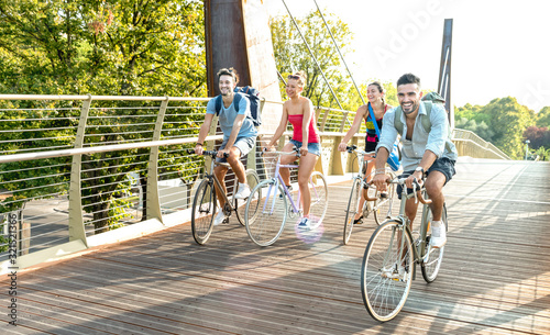 Happy millenial friends having fun riding bike at city park - Friendship concept Fototapeta
