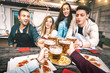 Leinwanddruck Bild - Point of view of young friends eating take away pizza at home patio after work - Friendship concept with happy people enjoying time together and having fun drinking brew pints - Focus on beer glasses