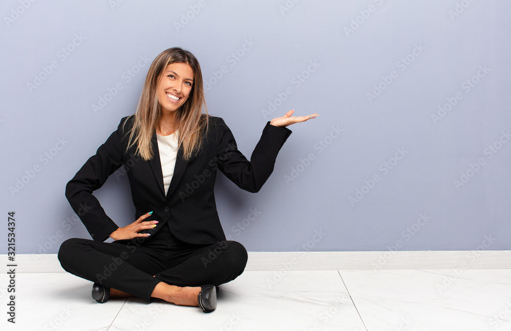 Fototapeta young pretty woman feeling happy and cheerful, smiling and welcoming you, inviting you in with a friendly gesture business concept