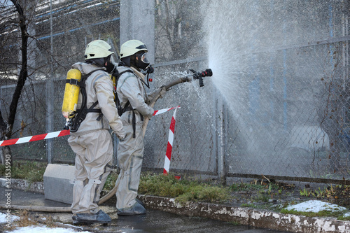 Photo Rescuers in protective rubber suits watering plant territory with syringe