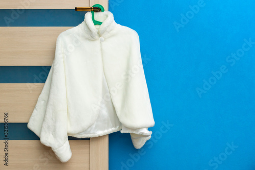 Fashionable white female coat hanging on door handle on blue wall background Wallpaper Mural