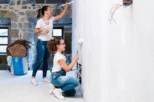 Mother And Daughter Painting A Wall Of Her New House Together
