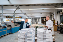 Two Businessmen At Stack Of Pa...