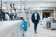 Businessman Walking In A Factory