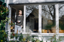 Man In Sunroom At Home Leaning...