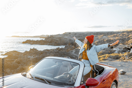 Woman enjoying beautiful view on the ocean, sitting with raised hands on the convertible car during a sunset Wallpaper Mural