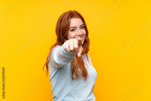 Obraz Teenager redhead girl over isolated yellow background points finger at you with a confident expression - fototapety do salonu