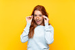Leinwanddruck Bild - Teenager redhead girl over isolated yellow background with glasses and surprised