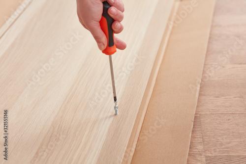 Fotografie, Tablou Woman assembling self-assembling furniture