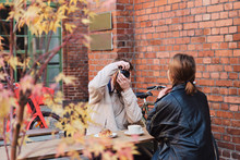 Young Man Taking Photo Of Girlfriend During Coffee Break In Cafe Outdoor