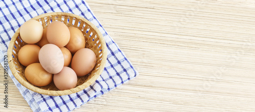 Photo Real farm chicken eggs lie in a wicker basket on the table