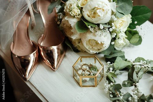 Wedding accessories on the dressing table: a bridal bouquet of white peonies, wedding rings in a glass box, gold shoes Poster Mural XXL