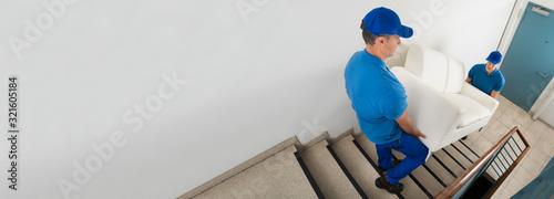 Fototapeta Two Movers Carrying Sofa On Staircase obraz