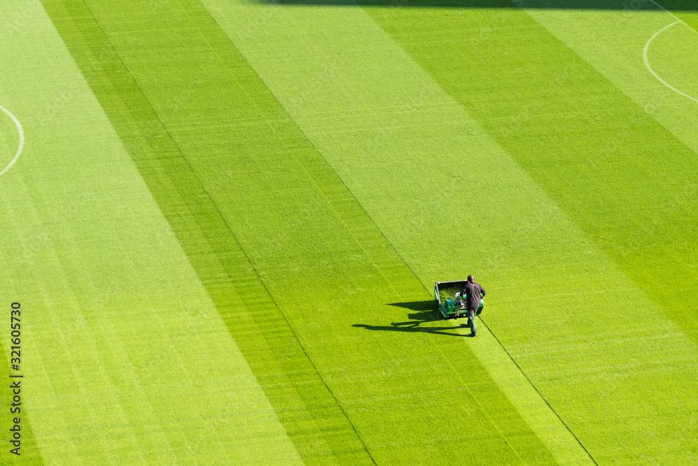 Osoba z sekatorem cięcia trawy na stadionie piłkarskim