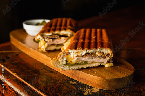 Fotografija Traditional cuban sandwich with cheese, ham and fried pork, served on a wooden b