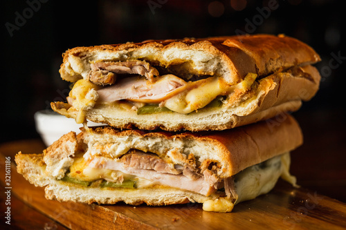 Foto Traditional cuban sandwich with cheese, ham and fried pork, served on a wooden b