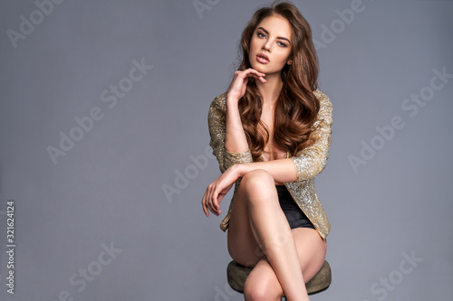 Obraz Portrait of a beautiful woman with a long hair in a golden shiny jacket. Young brunette woman in shiny sits on chair. Beautiful fashion model with brown hair, isolated on white background. - fototapety do salonu