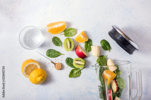Fotografie, Tablou Smoothie ingredients in mixer, smoothie preparation with spinach, apple, orange,