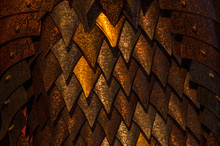 Metal Scales Of Different Shades Close Up. Background With Golden Rhombuses. Neutral Dark Background.
