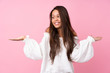 Young Brazilian girl over isolated pink background holding copyspace with two hands