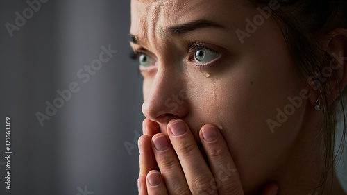 Photo Sad desperate grieving crying woman with folded hands and tears eyes during trou