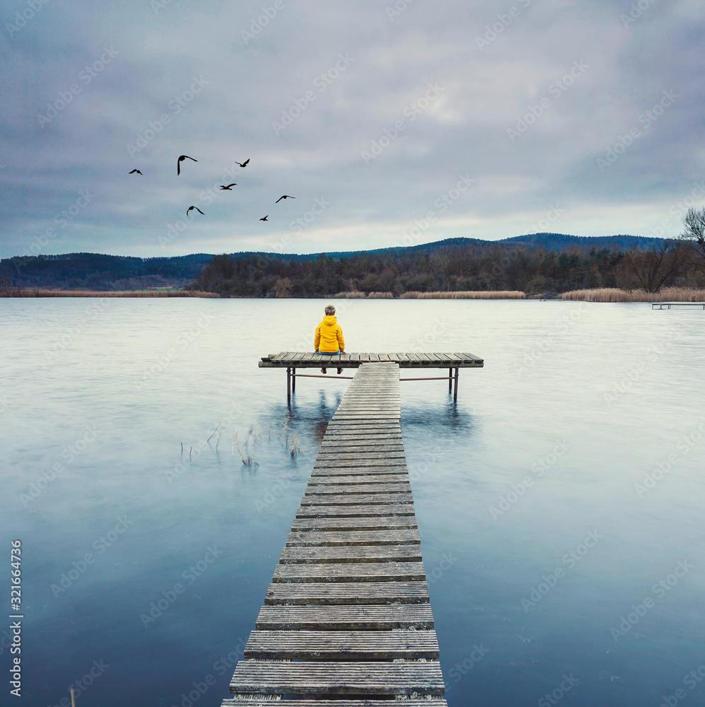 Fototapeta Frau sitzt einsam am See