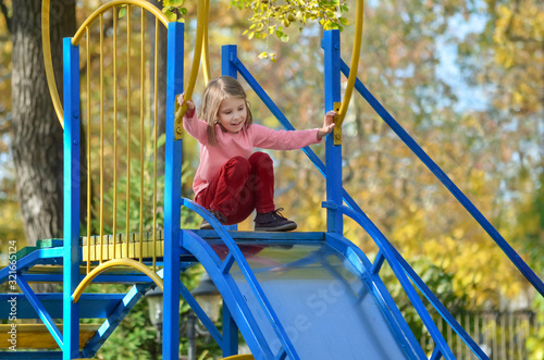 Little fair-haired girl has fun on a slide at the playground on a warm autumn day Tablou Canvas