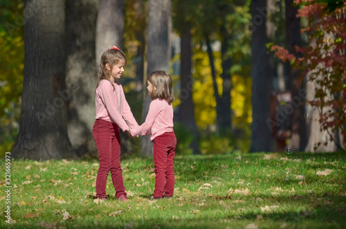 Valokuva Two little sisters in identical clothes hold each other's hands during a walk in the park on a warm autumn day