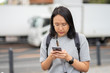 beautiful Asian woman Traveler uses a smartphone in the city center to search for various places. Restaurant reviews And send a message with copy space.
