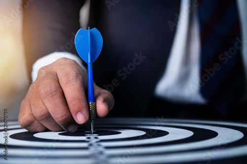 Fotomural target and strategy concept, businessman focus to aim by throwing dart on target