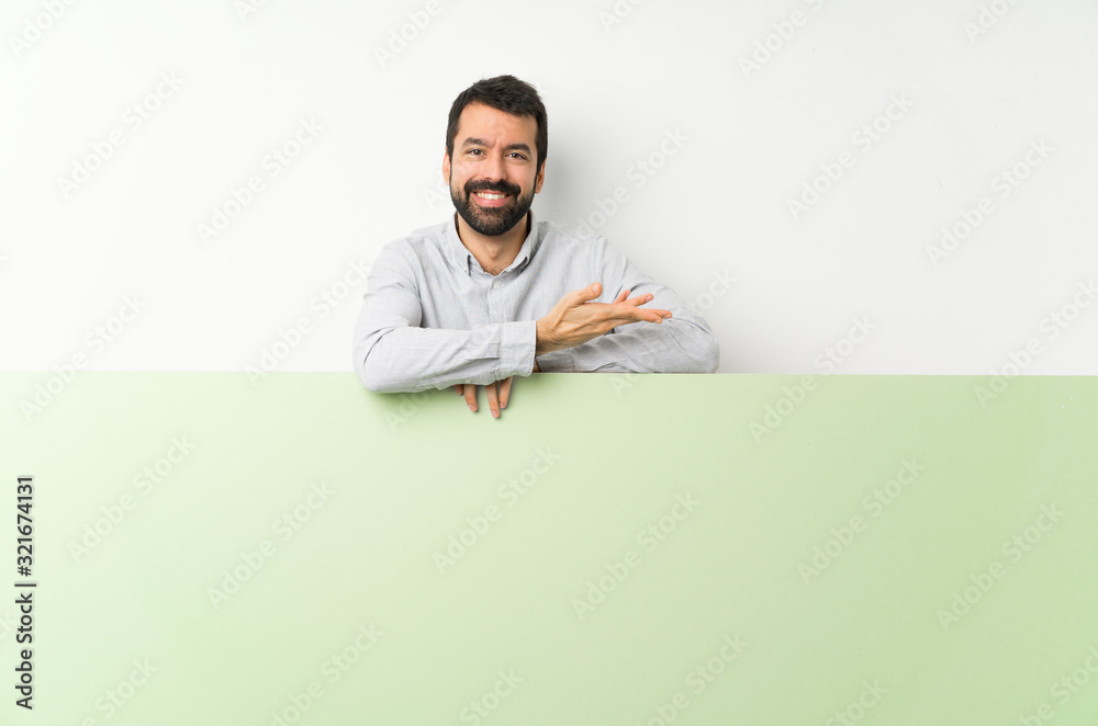 Fototapeta Young handsome man with beard holding a big green empty placard presenting an idea while looking smiling towards
