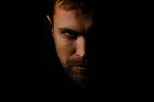 Male Evil Face. Portrait Of Evil On A Black Background. Dark Portrait Of A Man Looking Like A Devil. The Criminal Is Hiding