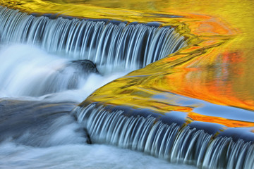Fototapeta Wodospad Bond Falls cascade captured with motion blur and illuminated by reflected color from sunlit autumn maples and blue sky overhead, Michigan's Upper Peninsula, USA