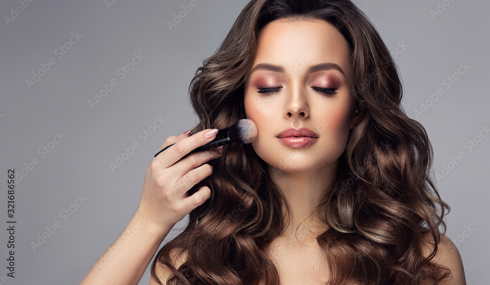 Fototapeta Makeup artist applies  Makeup artist applies   applies powder and blush  . Beautiful woman face. Hand of make-up master puts blush on cheeks  beauty  model girl . Make up in process  . Beautiful woman