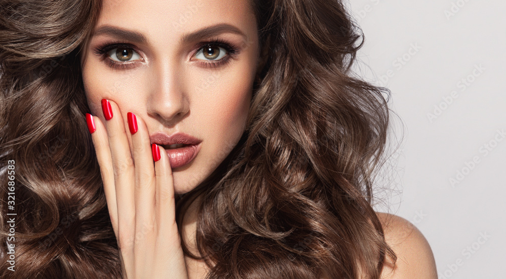 Fototapeta Beautiful model with long curly hair . Fashion trend image , the girl with red manicure on nails. Cosmetics ,makeup and wavy hairstyle
