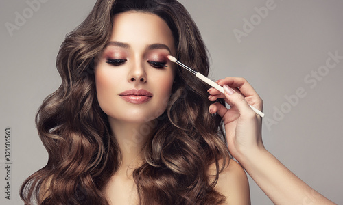 Obraz Makeup artist applies  eye shadow  . Beautiful woman with make-up face. Hand of visagiste, painting  cosmetics of young beauty  model girl . Make up in process - fototapety do salonu
