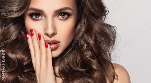 Beautiful model with long curly hair . Fashion trend image , the girl with red manicure on nails. Cosmetics ,makeup and wavy hairstyle