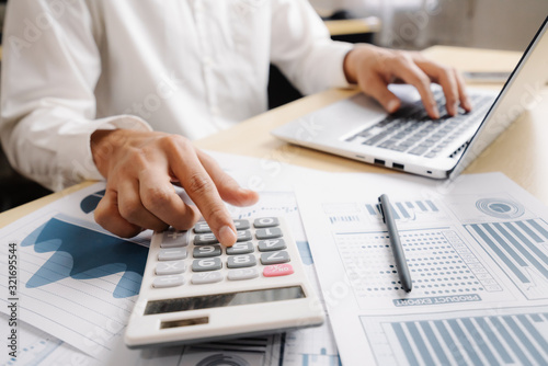 Fototapeta Businessman accountant or financial expert analyze business report graph and finance chart at corporate office. Concept of finance economy, banking business and stock market research. obraz