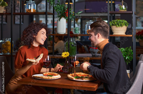 Fototapeta Young lovely couple is eating pizza it in pizzeria. guy is amuses his girl in a restaurant. Happy people having fun together obraz