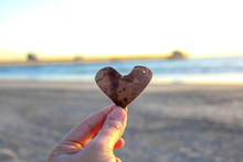 Hand Holding Heart In Front Of The Ocean And Pier In Oceanside California