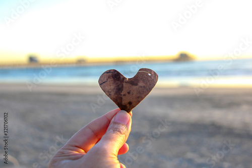 Canvas Print Hand holding heart in front of the ocean and pier in Oceanside California