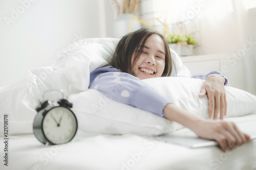 Obraz portrait happy young asian pretty woman in casual clothing smiling with tablet and alarm clock lying with pillow on bed in bedroom at home, lifestyle, good morning, holiday and joyful weekend concept - fototapety do salonu